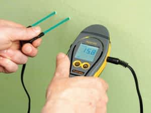 Mini 2000 Moisture Meter external probes into wall to measure for moisture
